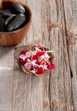Accesorios del balneario: piedras calientes para el masaje y las flores Fotos de archivo