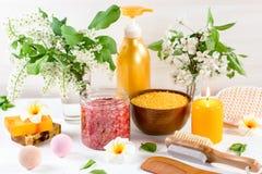 Accesorios del balneario y del baño con las sales de baño y productos del tratamiento de la belleza en la tabla blanca Concepto d imagenes de archivo