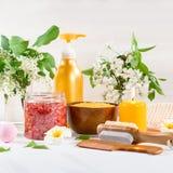 Accesorios del balneario y del ba?o con las sales de ba?o y productos del tratamiento de la belleza en la tabla blanca Concepto d fotografía de archivo