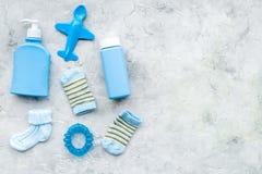 Accesorios del bebé azul Calcetines, juguetes, cosméticos en espacio gris de la copia de la opinión superior del fondo Imagenes de archivo