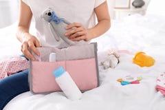 Accesorios del bebé de la mujer que embalan en el bolso de maternidad en cama imagenes de archivo
