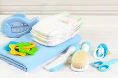 Accesorios del bebé en el fondo de madera blanco Foto de archivo libre de regalías