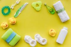 accesorios del bebé para el baño con el cosmético y los patos del cuerpo en maqueta amarilla de la opinión superior del fondo Fotos de archivo