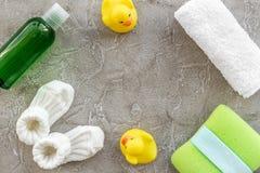 accesorios del bebé para el baño con el cosmético y los patos del cuerpo en maqueta gris de la opinión superior del fondo Imagen de archivo libre de regalías