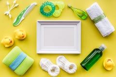 Accesorios del bebé para el baño con el cosmético, el marco y los patos del cuerpo en maqueta amarilla de la opinión superior del Fotografía de archivo libre de regalías