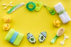 accesorios del bebé para el baño con el cosmético y los patos del cuerpo en maqueta amarilla de la opinión superior del fondo Fotografía de archivo