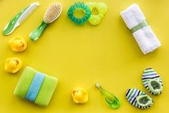 accesorios del bebé para el baño con el cosmético y los patos del cuerpo en maqueta amarilla de la opinión superior del fondo Foto de archivo libre de regalías