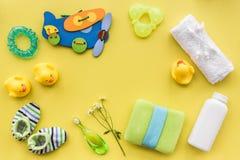 accesorios del bebé para el baño con el cosmético y los patos del cuerpo en maqueta amarilla de la opinión superior del fondo Foto de archivo