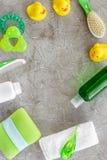 accesorios del bebé para el baño con el cosmético y los patos del cuerpo en maqueta gris de la opinión superior del fondo Fotos de archivo libres de regalías