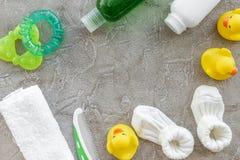 accesorios del bebé para el baño con el cosmético y los patos del cuerpo en maqueta gris de la opinión superior del fondo Foto de archivo