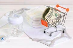 Accesorios del bebé y cesta de compras en el fondo de madera blanco Imagenes de archivo