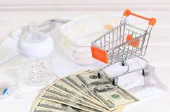 Accesorios del bebé y cesta de compras en el fondo de madera blanco Fotos de archivo
