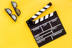Accesorios del cineasta Clapperboard y vidrios en copyspace amarillo de la opinión superior del fondo Imagenes de archivo