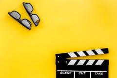 Accesorios del cineasta Clapperboard y vidrios en copyspace amarillo de la opinión superior del fondo fotografía de archivo libre de regalías