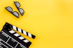 Accesorios del cineasta Clapperboard y vidrios en copyspace amarillo de la opinión superior del fondo Fotos de archivo