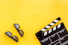 Accesorios del cineasta Clapperboard y vidrios en copyspace amarillo de la opinión superior del fondo imagen de archivo libre de regalías