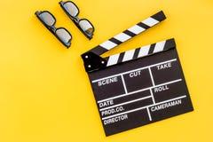 Accesorios del cineasta Clapperboard y vidrios en copyspace amarillo de la opinión superior del fondo imagen de archivo