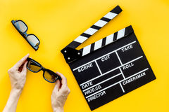 Accesorios del cineasta Clapperboard y vidrios en la opinión superior del fondo amarillo imagenes de archivo