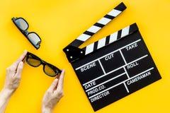 Accesorios del cineasta Clapperboard y vidrios en la opinión superior del fondo amarillo imagen de archivo