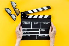 Accesorios del cineasta Clapperboard y vidrios en la opinión superior del fondo amarillo fotografía de archivo libre de regalías