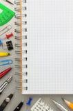 Accesorios del cuaderno y de la escuela en el fondo del metal Imágenes de archivo libres de regalías