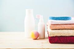 Accesorios del cuarto de baño - toallas, crema, espuma del baño y champúes en una luz, concepto brillante del fondo de cuidar par Imagen de archivo
