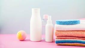 Accesorios del cuarto de baño - toallas, crema, espuma del baño y champúes en una luz, concepto brillante del fondo de cuidar par Imagenes de archivo