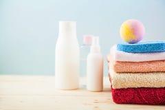 Accesorios del cuarto de baño - toallas y champúes, espuma del baño, crema en una luz, fondo azul y rosado brillante el concepto  Imágenes de archivo libres de regalías