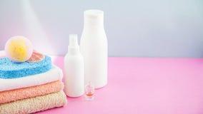 Accesorios del cuarto de baño - toallas y champúes, espuma del baño, crema en una luz, fondo azul y rosado brillante el concepto  Fotos de archivo