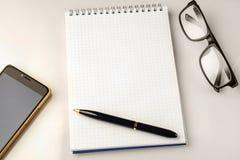 Accesorios del espacio de trabajo: pluma, cuaderno, vidrios y un smartphone moderno Imagen de archivo libre de regalías