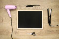 Accesorios del Hairstyling con la pizarra en fondo de madera Foto de archivo libre de regalías