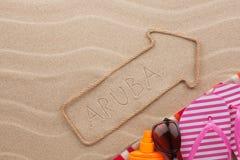 Accesorios del indicador y de la playa de Aruba que mienten en la arena Fotografía de archivo libre de regalías