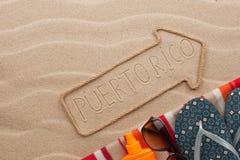 Accesorios del indicador y de la playa de Puerto Rico que mienten en la arena Fotos de archivo libres de regalías