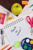 Accesorios del libro y de la escuela en los tableros blancos, de nuevo a concepto de la escuela Fotos de archivo libres de regalías