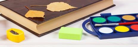 Accesorios del libro y de la escuela en los tableros blancos, de nuevo a concepto de la escuela Imagen de archivo libre de regalías