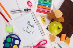 Accesorios del libro y de la escuela en los tableros blancos, de nuevo a concepto de la escuela Fotos de archivo
