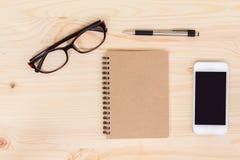 Accesorios del móvil y de la oficina en el fondo de madera Imágenes de archivo libres de regalías