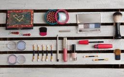Accesorios del maquillaje en el fondo de madera blanco Imagen de archivo