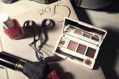 Accesorios del maquillaje y calendario de la fecha Imagen de archivo libre de regalías