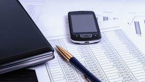 Accesorios del negocio en el escritorio con los documentos financieros Imagen de archivo