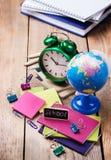 Accesorios del negocio, fuentes, despertador, lápices en la tabla de madera rústica Imágenes de archivo libres de regalías