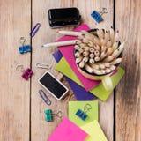 Accesorios del negocio, fuentes, taza con los lápices en la tabla de madera rústica Fotos de archivo libres de regalías