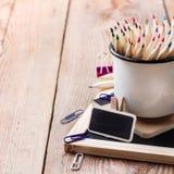Accesorios del negocio, fuentes, taza con los lápices en la tabla de madera rústica Imagen de archivo