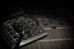Accesorios del negocio (lupa, calculadora) y gráficos, tablas, cartas en una tabla con el fondo oscuro Foco selectivo Imagen de archivo libre de regalías