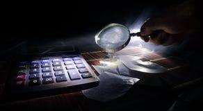 Accesorios del negocio (lupa, calculadora) y gráficos, tablas, cartas en una tabla con el fondo oscuro Foco selectivo Foto de archivo