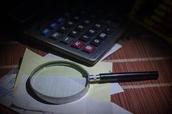 Accesorios del negocio (lupa, calculadora) y gráficos, tablas, cartas en una tabla con el fondo oscuro Foco selectivo Foto de archivo libre de regalías