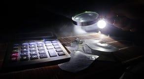 Accesorios del negocio (lupa, calculadora) y gráficos, tablas, cartas en una tabla con el fondo oscuro Foco selectivo Fotos de archivo libres de regalías