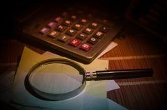 Accesorios del negocio (lupa, calculadora) y gráficos, tablas, cartas en una tabla con el fondo oscuro Foco selectivo Imagenes de archivo