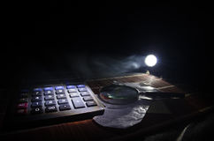 Accesorios del negocio (lupa, calculadora) y gráficos, tablas, cartas en una tabla con el fondo oscuro Foco selectivo Fotografía de archivo