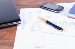 Accesorios del negocio - una pluma, un teléfono y ordenador portátil en el escritorio con los documentos financieros Imagenes de archivo